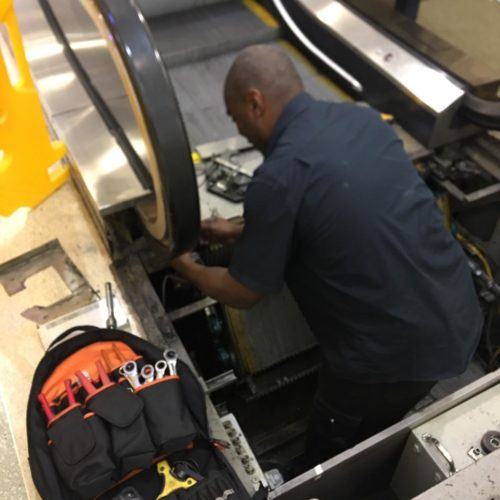 AMS employee carrying out escalator repairs